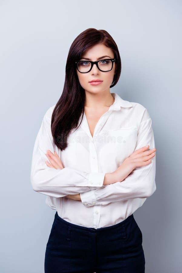 Photo de femme d'affaires stricte dans l'uniforme se tenant avec h croisé image libre de droits