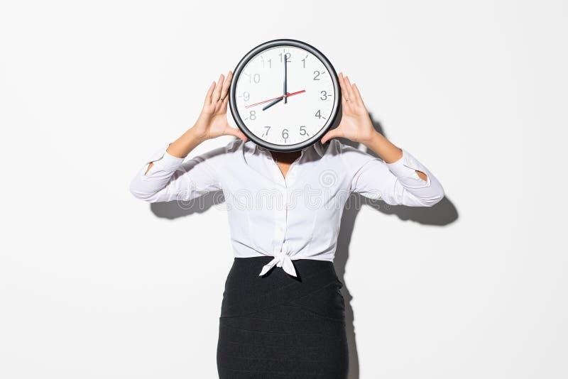 Photo de femme drôle dans la chemise blanche et de visage noir de bâche de jupe avec la grande horloge ronde d'isolement au-dessu image libre de droits