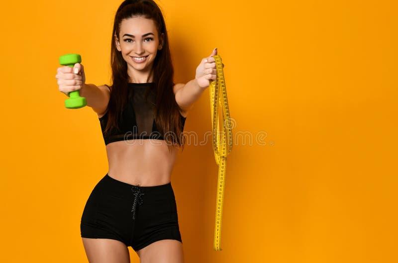 Photo de femme musculaire dans les vêtements de sport sur le fond jaune photographie stock libre de droits