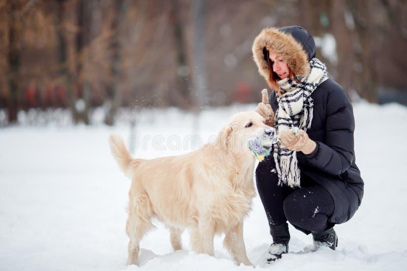 Photo de femme de sourire s'accroupissant à côté de Labrador avec le jouet dans des dents en hiver images stock