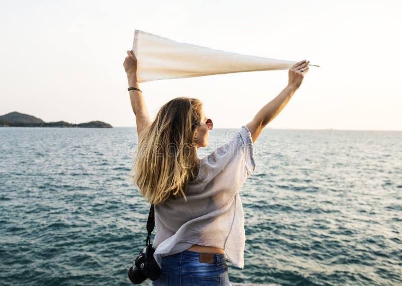 Photo de femme utilisant les fonds supérieurs et bleus blancs et la caméra noire de Dslr tenant le textile blanc tout en faisant  photographie stock libre de droits