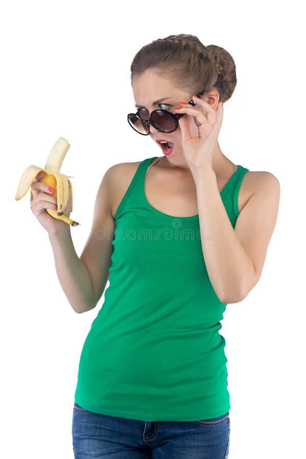 Photo de fille étonnée avec la banane et les lunettes de soleil photo libre de droits