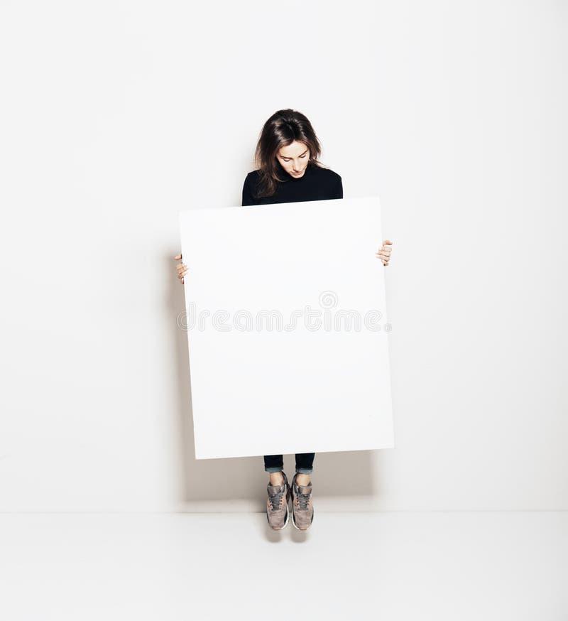 Photo de fille sautant dans la galerie moderne et regardant la toile blanche vide Horizontal, maquette images stock