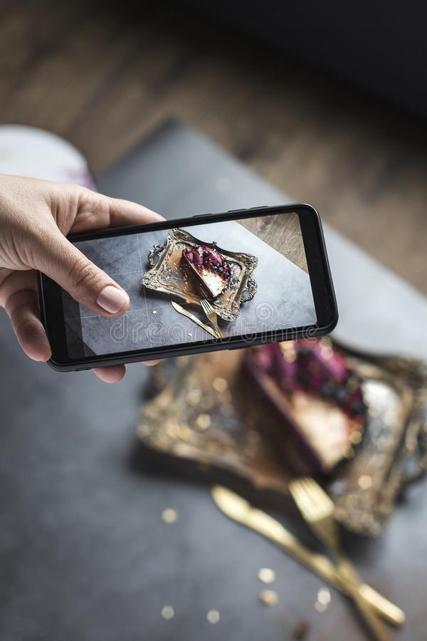 Photo de gâteau et de vaisselle au téléphone une main femelle avec la belle manucure Fond gris photo stock