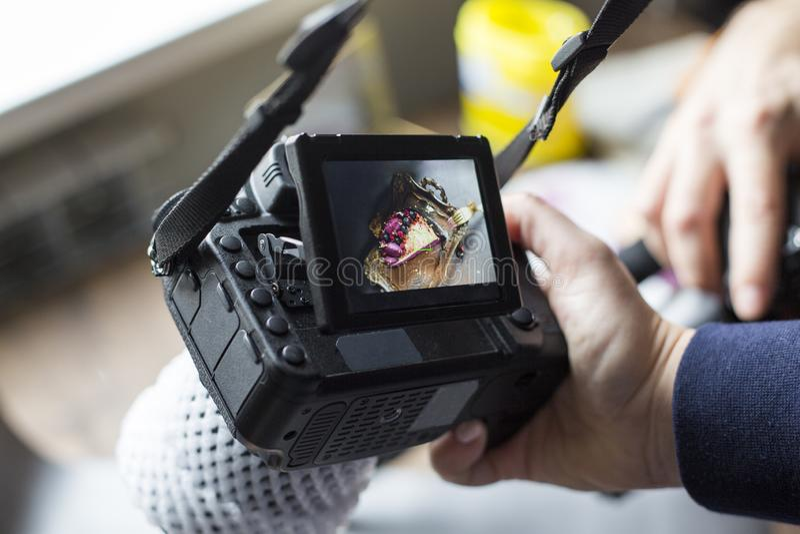 Photo de gâteau sur l'écran de caméra la fille tient la caméra à disposition photo stock