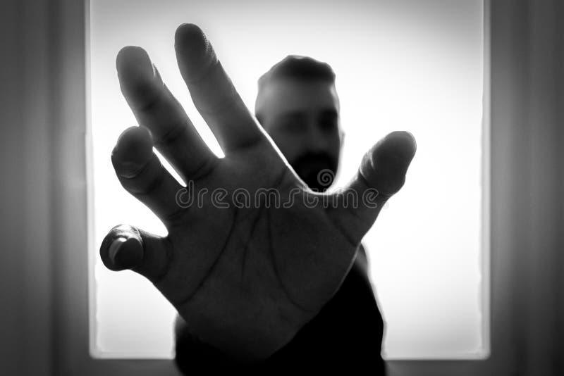 Photo de gamme de gris de l'homme saisissant utilisant la main droite photo stock