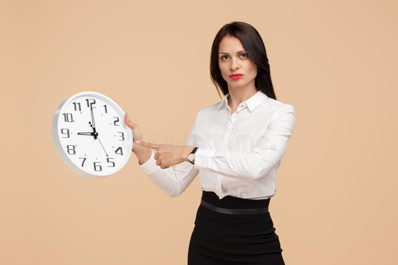 Photo de jeune doigt moderne malheureux de point de femme d'affaires à une horloge au-dessus de fond beige images libres de droits