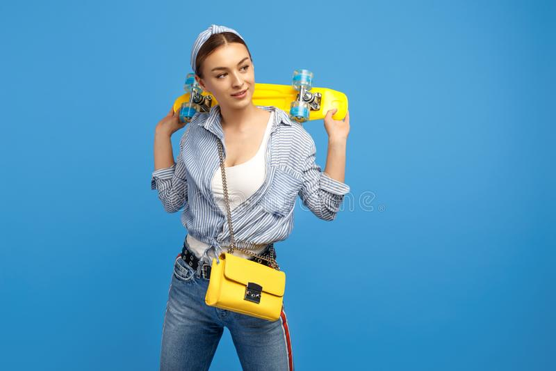 Photo de jeune femme adorable avec le penny jaune ou de planche à roulettes posant au-dessus du fond bleu image libre de droits