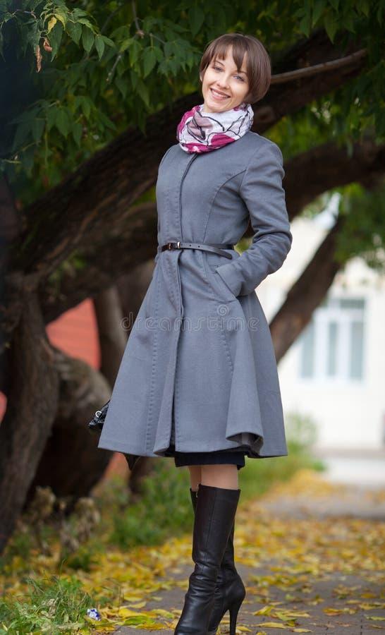 Photo de jeune femme de sourire dans le manteau gris image stock
