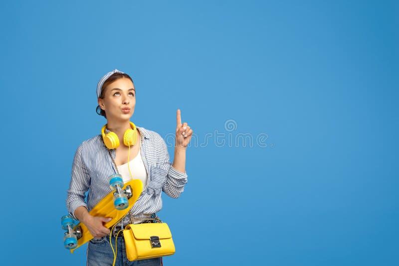 Photo de jeune femme gaie avec les écouteurs jaunes posant avec le penny ou la planche à roulettes et le doigt de point au-dessus photographie stock
