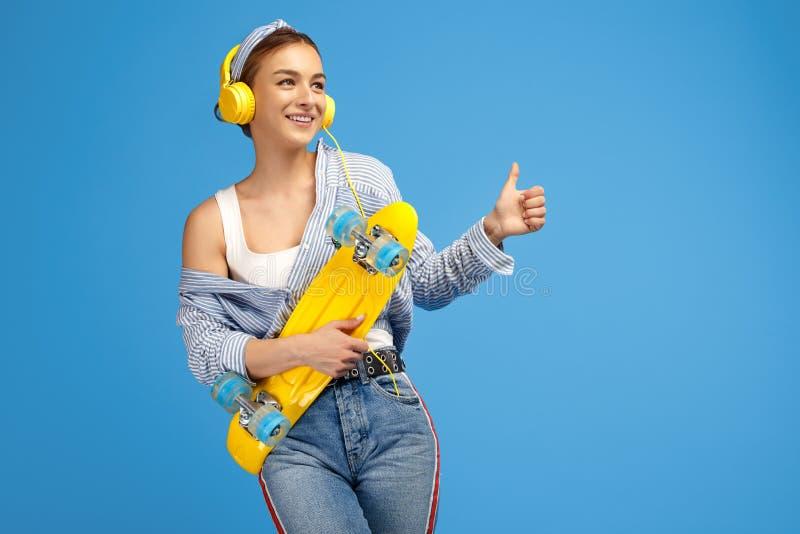 Photo de jeune femme gaie avec les écouteurs jaunes posant avec le penny ou la planche à roulettes et montrant le bon geste au-de images libres de droits