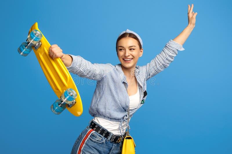 Photo de jeune femme heureuse avec la danse jaune de penny ou de planche à roulettes au-dessus du fond bleu images libres de droits