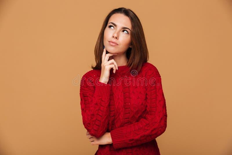 Photo de jeune jolie fille réfléchie avec du charme dans le chandail rouge à images stock