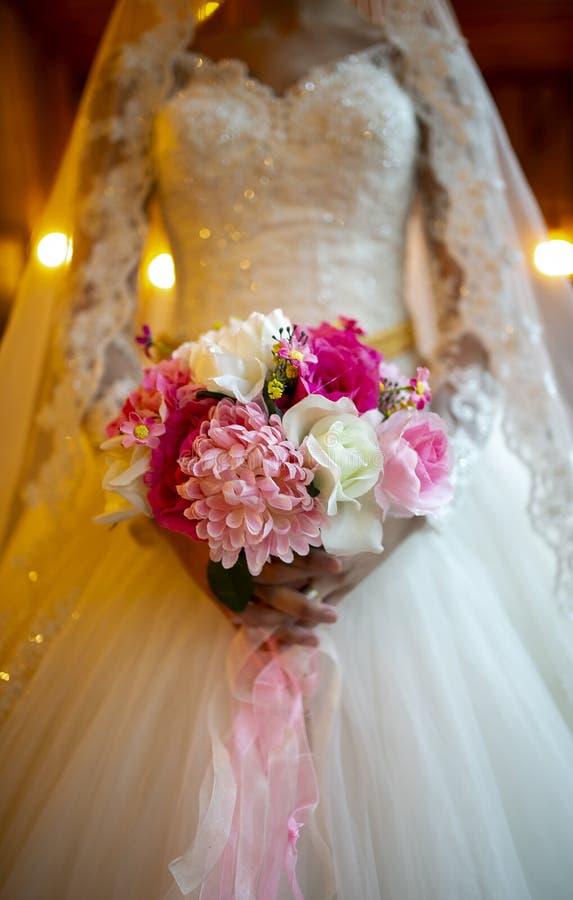 Photo de jeune mariée indiquant l'avant de la fleur dans sa main photographie stock