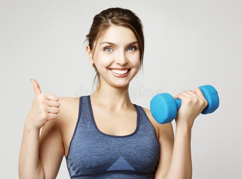 Photo de l'ajustement et de la jeune femme en bonne sant? souriant et tenant le dumbbelsl sur l'?paule Sport et concept de person image libre de droits