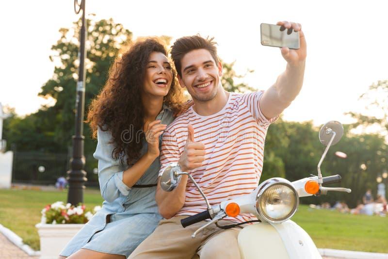 Photo de l'homme et de la femme prenant le selfie au téléphone portable tout en se reposant ensemble sur la motocyclette en parc  photographie stock