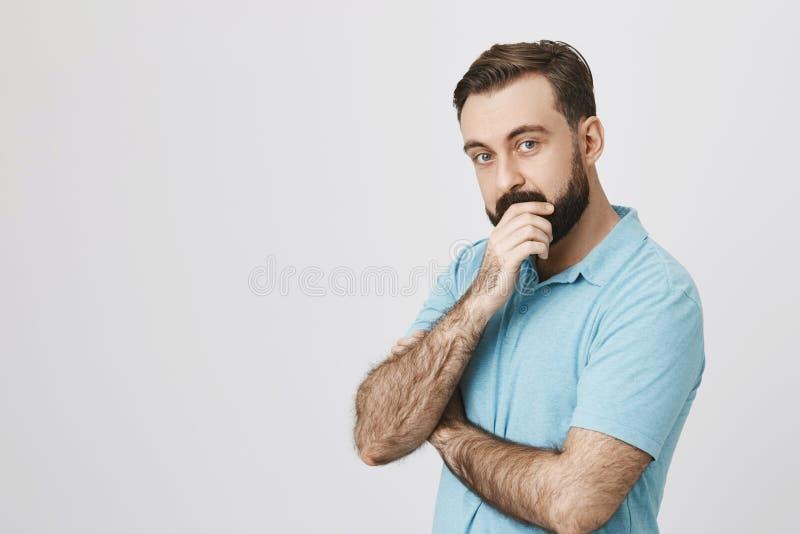 Photo de l'homme semblant curieuse touchant sa barbe se tenant à côté du mur blanc Le type beau a juste eu une idée comment à photographie stock