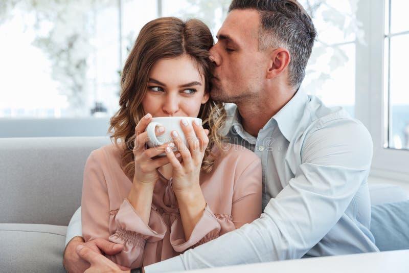 Photo de l'homme de soin adulte étreignant et embrassant son amie i image stock