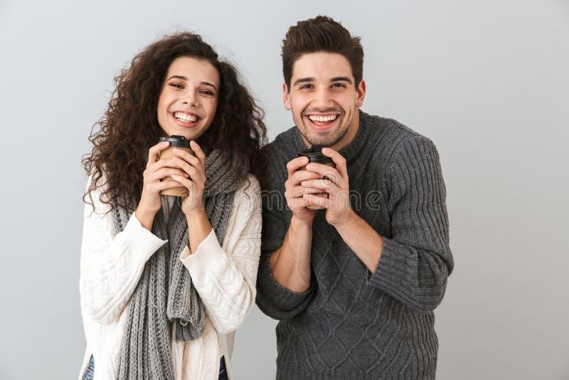 Photo de l'homme de sourire de couples et des écharpes de port de femme tenant des tasses avec le thé ou le café chaud, d'isoleme photo stock