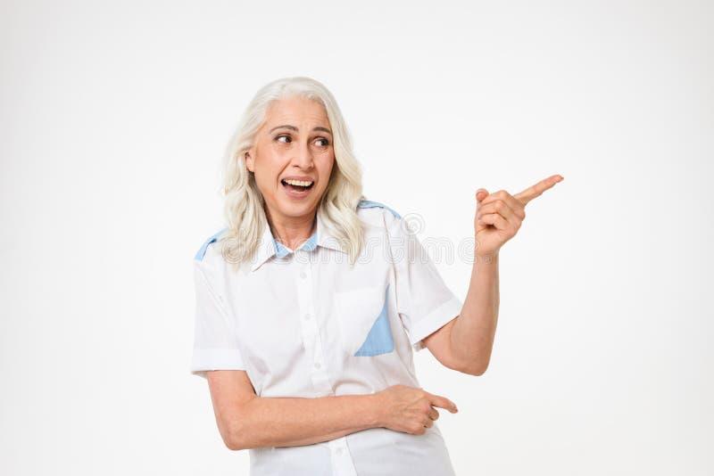 Photo de la femme adulte avec les cheveux gris souriant et regardant de côté images libres de droits