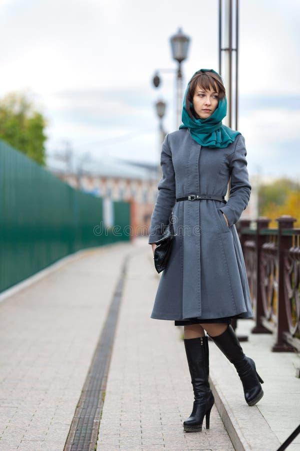 Photo de la femme dans le manteau gris marchant sur la chaussée photo libre de droits