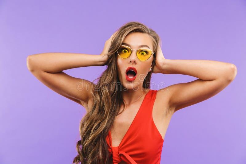 Photo de la femme effrayée ou choquée 20s portant la robe et le sungl rouges images stock