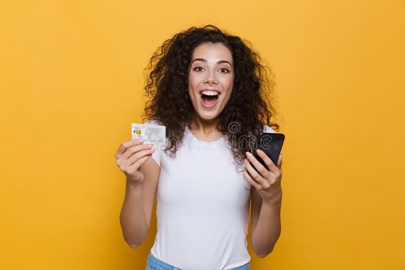 Photo de la femme magnifique 20s portant les vêtements sport tenant Mobil photos libres de droits