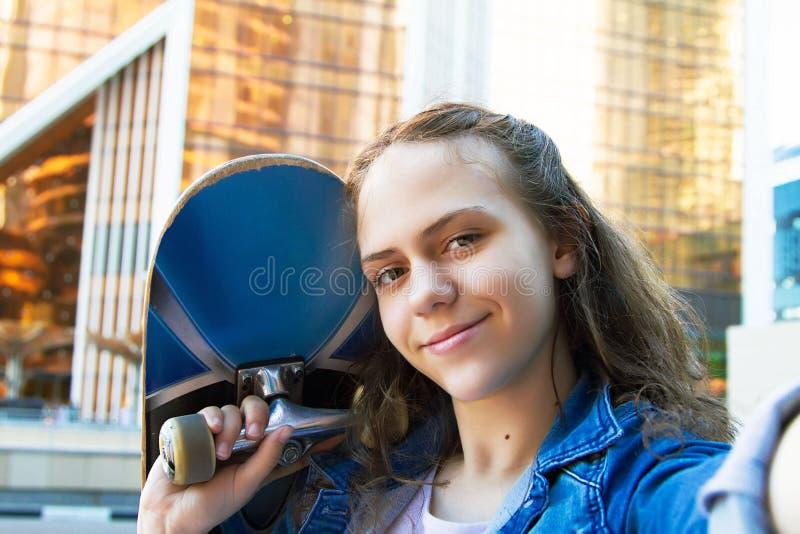 Photo de la fille heureuse d'étudiant tenant une planche à roulettes sur son épaule photographie stock libre de droits