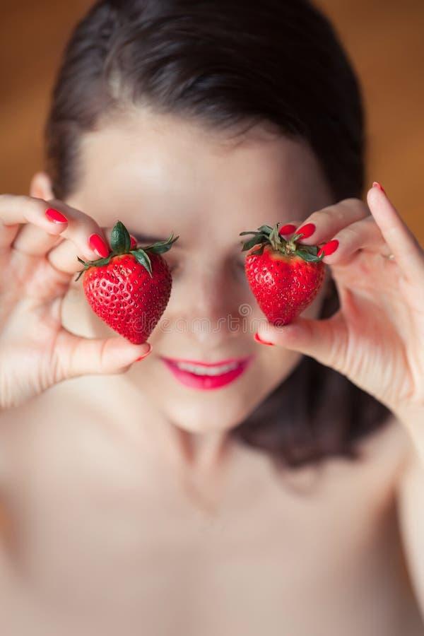 Photo de la fraise se tenante femelle séduisante près des eyeys de visage, Cl photographie stock libre de droits