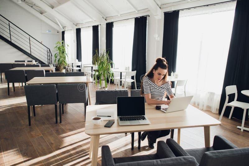 Photo de la jeune belle femme s'asseyant à une table avec un ordinateur portable et tenant le smartphone, tandis que son assistan images stock