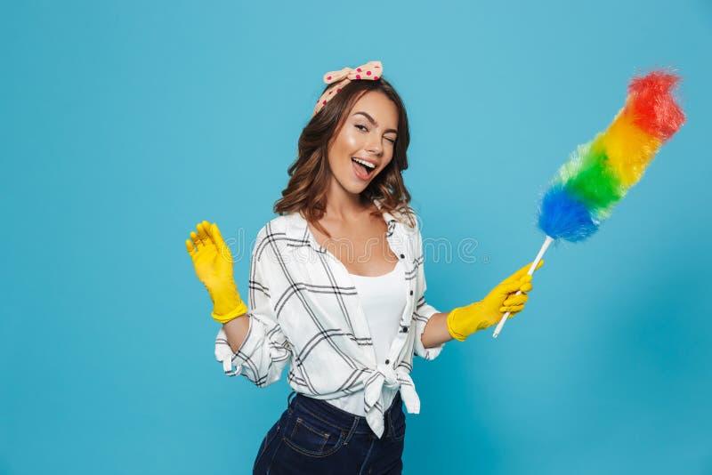 Photo de la jeune femme au foyer gaie 20s dans les gants en caoutchouc jaunes FO photos libres de droits