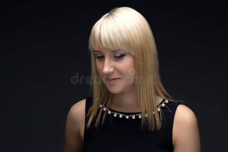 Photo de la jeune femme blonde regardant vers le bas photographie stock