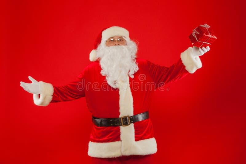 Photo de main enfilée de gants de Santa Claus avec le giftbox, sur un backgrou rouge image stock