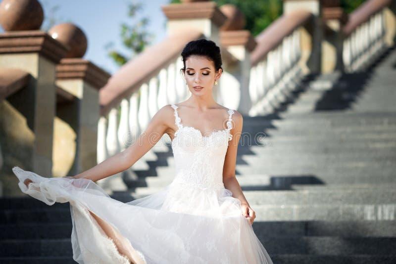 Photo de mode de belle femme avec les cheveux foncés dans la robe l'épousant luxueuse photographie stock libre de droits
