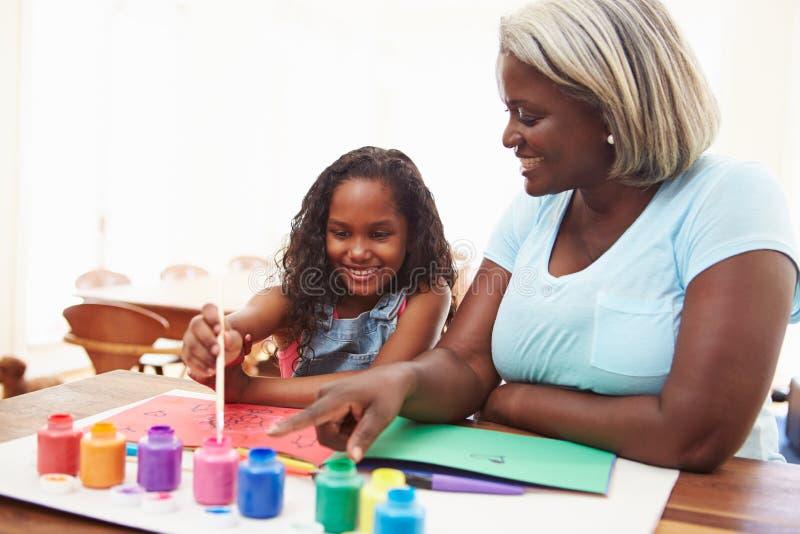 Photo de peinture de grand-mère avec la petite-fille à la maison photo stock