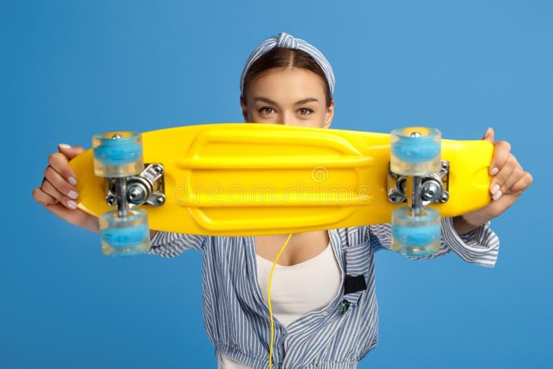 Photo de penny jaune de belle prise de jeune femme ou planche à roulettes devant le visage au-dessus du fond bleu photos stock
