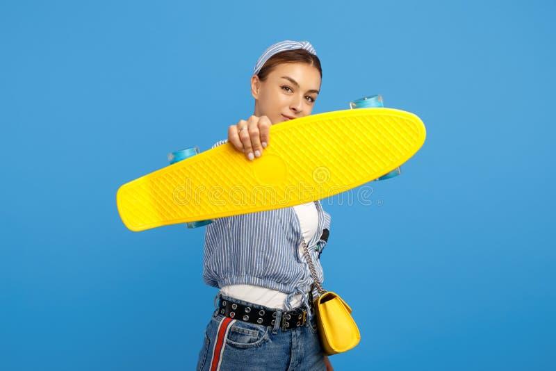 Photo de penny jaune de belle prise de jeune femme ou planche à roulettes devant le visage au-dessus du fond bleu images stock