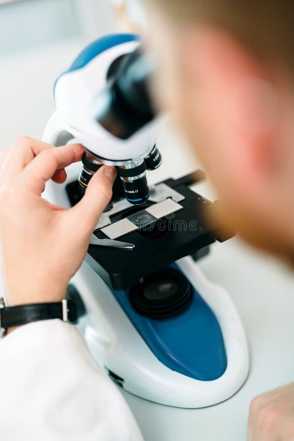 Photo de plan rapproché de chercheur regardant par le microscope images stock