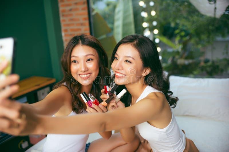 Photo de plan rapproché des filles drôles mignonnes tenant le vernis photo libre de droits
