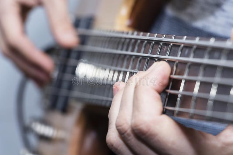 Photo de plan rapproché des mains de joueur de guitare basse, foyer sélectif mou, thème de musique en direct photographie stock