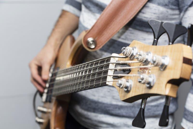 Photo de plan rapproché des mains de joueur de guitare basse, foyer sélectif mou, thème de musique en direct photographie stock libre de droits