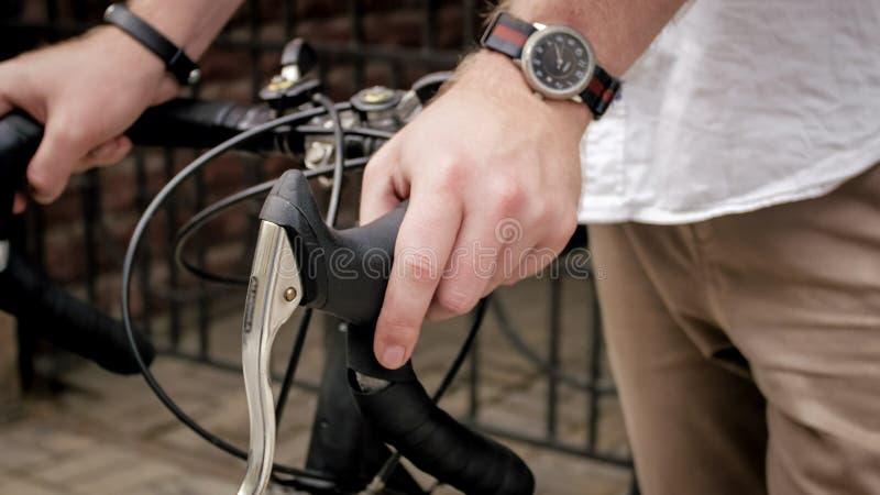 Photo de plan rapproché des montres de l'homme et du traqueur de port de forme physique tenant la main sur la vieille bicyclette photographie stock