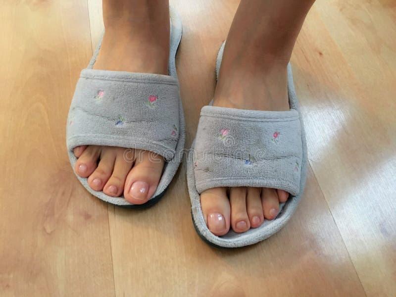 Photo de plan rapproché des pieds de femme en sandale grise de pantoufle image libre de droits