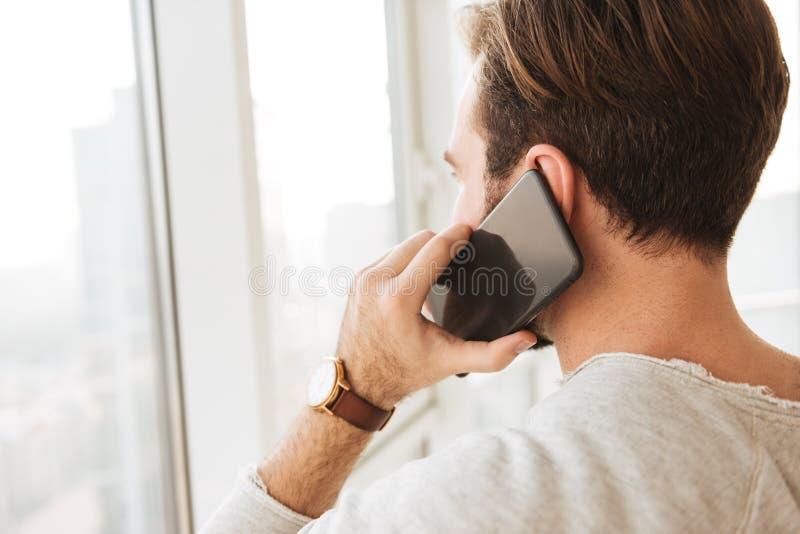 Photo de plan rapproché de dos de l'homme avec les cheveux foncés courts regardant le thro image stock