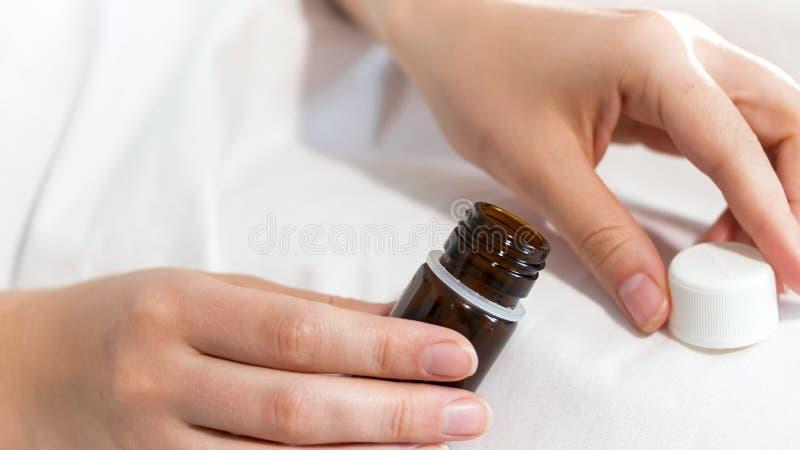 Photo de plan rapproché de femme jugeant le récipient avec des pilules disponible images stock