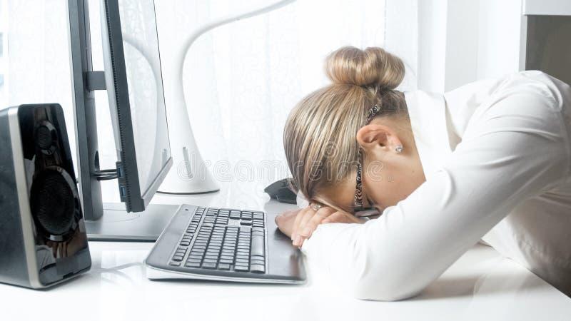 Photo de plan rapproché de jeune femme d'affaires dormant sur le bureau photographie stock