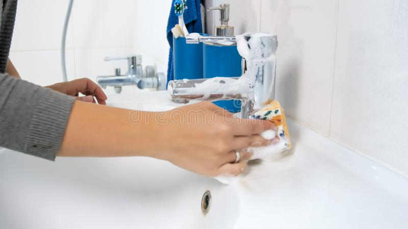 Photo de plan rapproché de jeune robinet d'évier de nettoyage de femme au foyer avec le détergent photos libres de droits