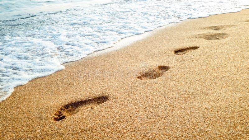 Photo de plan rapproch? des vagues de mer calme lavant outre des empreintes de pas humaines sur le sable humide ? la plage ar?nac photographie stock