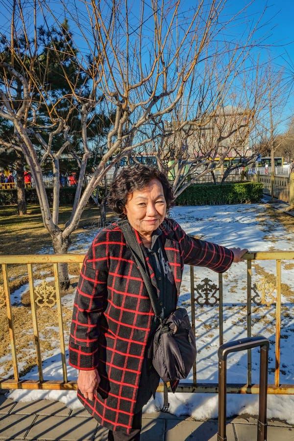 Photo de portrait des femmes asiatiques supérieures avec la neige au sol dans la capitale de Pékin photographie stock