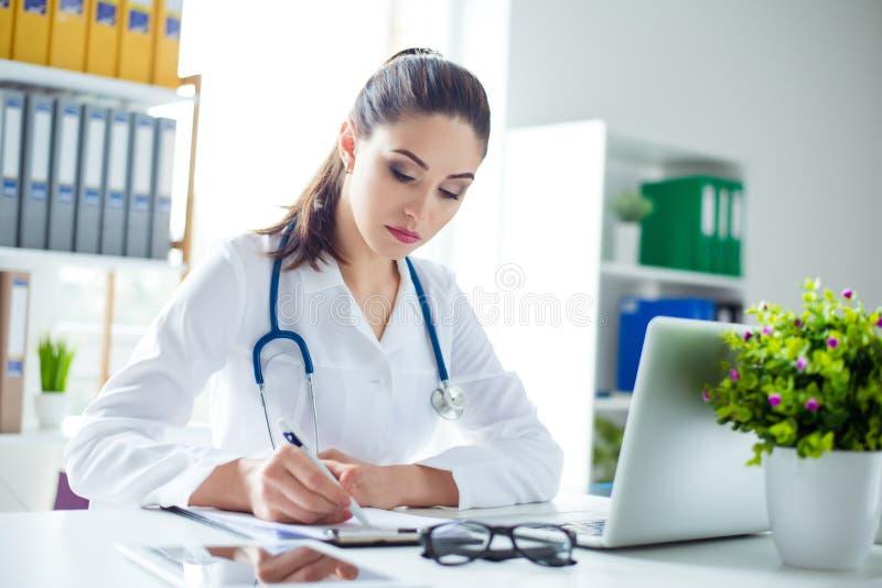Photo de prescription femelle concentrée attrayante d'écriture de docteur photographie stock libre de droits